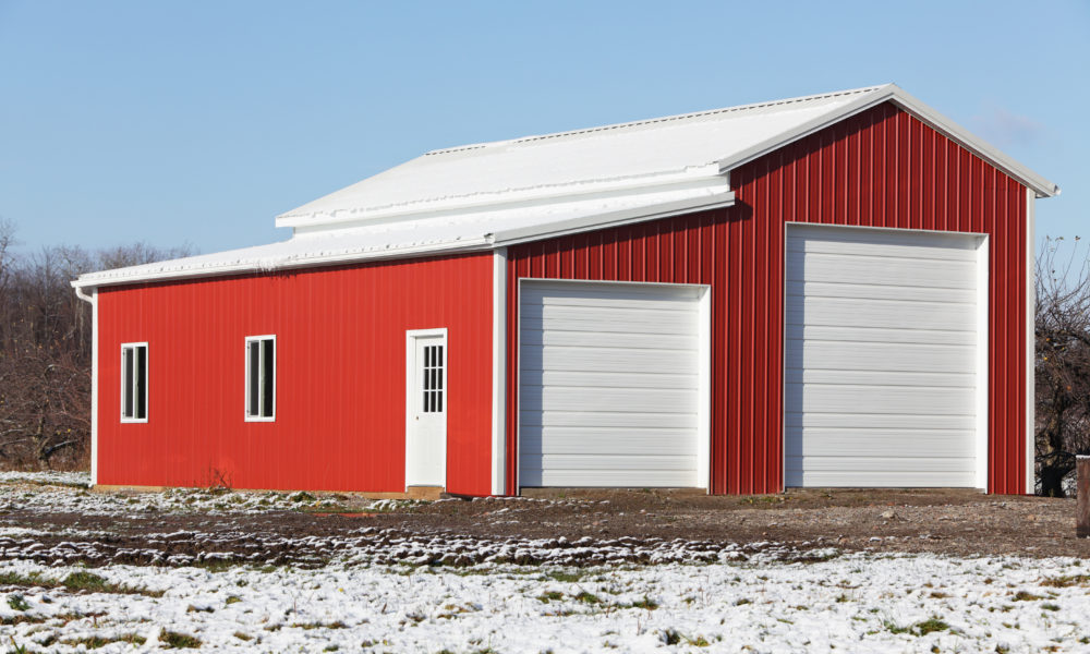 In early winter, construction is almost complete on this brand new, bright red and white corrugated metal warehouse/vehicle storage building on a rural road at the edge of a large apple orchard in western New York state, USA. Apple trees can be seen in the background.